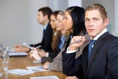 Una squadra di 5 genti di affari con il giovane maschio alla parte anteriore Immagine Stock