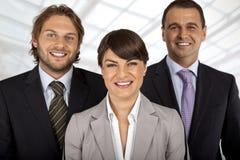 Una squadra positiva di affari di tre Immagini Stock
