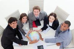 Una squadra varia di affari che tiene un glob terrestre Fotografia Stock Libera da Diritti