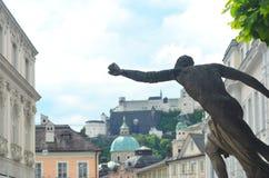 Una statua allunga il suo braccio attraverso la priorità alta di un quadrato vicino al castello di Salisburgo fotografia stock libera da diritti