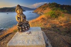 Una statua antica di Buddha dell'oro vicino all'oceano Fotografie Stock