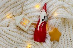 Una statua ceramica di Santa Claus su una sciarpa tricottata Fotografia Stock