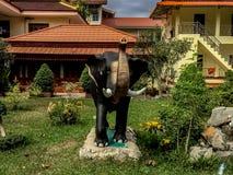 Una statua dell'elefante che si siede davanti ad un mortaio giallo che sviluppa w fotografie stock