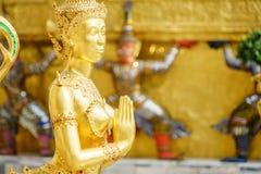 Una statua dorata di Kinnari nell'azione di sawasdee al tempio di Emerald Buddha (Wat Phra Kaew) Immagine Stock Libera da Diritti