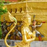 Una statua dorata di Kinnari nell'azione di sawasdee al tempio di Emerald Buddha (Wat Phra Kaew) Fotografia Stock Libera da Diritti