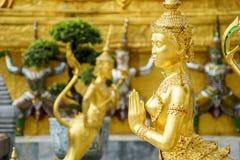 Una statua dorata di Kinnari nell'azione di sawasdee al tempio di Emerald Buddha (Wat Phra Kaew) Fotografia Stock