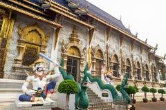 Una statua gigante davanti alla bella costruzione tailandese di stile in un tempio buddista in Tailandia fotografie stock