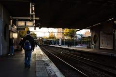 Una stazione ferroviaria con qualche gente intorno Fotografia Stock Libera da Diritti