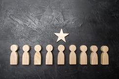 Una stella sopra una persona che sta in una fila tra altra gente Figurine di legno Il concetto di un segno di distinzione, succes immagine stock