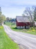 Una strada campestre e un granaio rosso rustico nel Michigan S.U.A. Immagine Stock Libera da Diritti