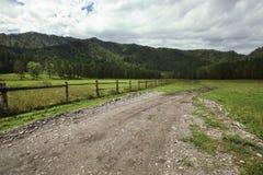 Una strada campestre lungo un recinto di legno conduce ad una distanza alle montagne Immagine Stock