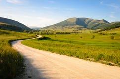 Una strada della montagna con il supporto Pennino nei precedenti Fotografia Stock Libera da Diritti