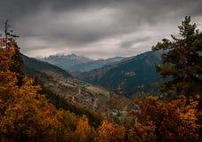 Una strada di bobina attraversa i villaggi nella Georgia contro lo sfondo delle montagne Fotografia Stock