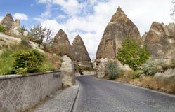 Una strada di bobina dalle pietre per lastricati passa vicino alle case di pietra del cono nelle rocce antiche di Goreme, Kappado Fotografia Stock