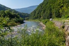 Una strada di bobina lungo il fiume veloce contro il contesto delle catene montuose verdi orgomous Fotografia Stock Libera da Diritti