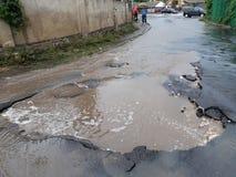 Una strada distrutta dopo una pioggia persistente immagine stock