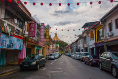 Una strada e case sulla via, la costruzione nella distanza Dewan Undangan Negeri Sarawak Kuching borneo malaysia Immagini Stock Libere da Diritti