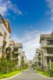 Una strada e due righe di nuove case del terrazzo Immagini Stock Libere da Diritti
