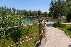 Una strada ha allineato con una grande pietra con le rotaie di legno, conducenti ad un lago trasparente verde della montagna Immagine Stock