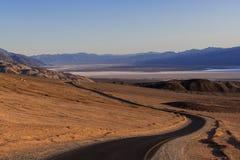 Una strada principale curva attraverso un vasto, paesaggio sterile del deserto immagini stock libere da diritti