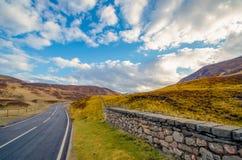 Una strada principale tipica attraverso una valletta scozzese che conduce con fotografia stock