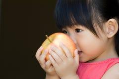 Una stretta del piccolo bambino una mela rossa Fotografia Stock