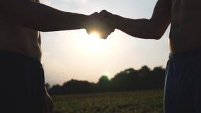 Una stretta di mano amichevole di due uomini bianchi muscolari irriconoscibili con lustro del sole a fondo Agitazione delle armi  Fotografia Stock