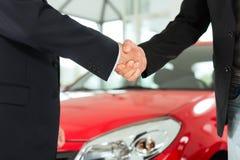 Una stretta di mano di due uomini in vestiti con un'automobile rossa Fotografia Stock Libera da Diritti