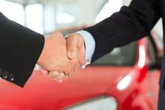 Una stretta di mano di due uomini in vestiti con un'automobile rossa Fotografie Stock