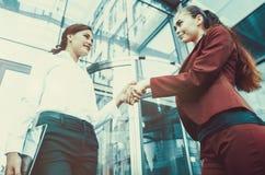 Una stretta di mano di due ragazze contro lo sfondo di un multi--s Fotografia Stock
