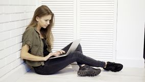 Una studentessa concentrata giovani sta lavorando con il computer portatile che si siede sul pavimento Fotografia Stock