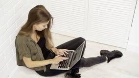 Una studentessa di modello graziosa sorridente dei giovani sta lavorando con il computer portatile che si siede sul pavimento con Immagine Stock