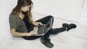 Una studentessa di modello graziosa sorridente dei giovani sta lavorando con il computer portatile che si siede sul pavimento con Immagini Stock Libere da Diritti