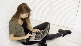 Una studentessa di modello graziosa sorridente dei giovani sta lavorando con il computer portatile che si siede sul pavimento con Immagine Stock Libera da Diritti