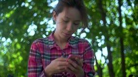 Una studentessa felice che usa uno smartphone in un parco cittadino seduto su una panchina, una giovane donna che sorride usa una stock footage