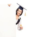 Una studentessa laureata felice con un'insegna bianca Immagini Stock Libere da Diritti