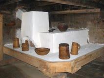 Una stufa di pietra antica nella capanna antica dello slavo Utensili da cucina di legno per cucinare La tradizione dei nostri ant fotografia stock