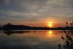 Una subida de oro hermosa de la puesta del sol/del sol en el lago Fondo del paisaje Imagen de archivo libre de regalías