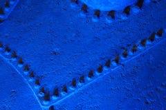 Una superficie de metal áspera con los remaches en la iluminación azul fotos de archivo