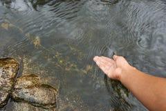 Una superficie natural del agua del tacto de la mano Fotografía de archivo