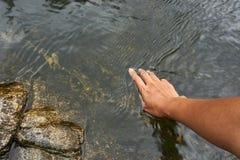 Una superficie natural del agua del tacto de la mano Fotografía de archivo libre de regalías