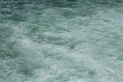 Una superficie pulita ma spumosa dell'acqua con il tono verde smeraldo di colore Immagine Stock