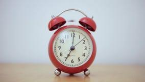 Una sveglia rossa d'annata gioca l'allarme quando l'ago del quadrante ottiene a 7 in punto stock footage