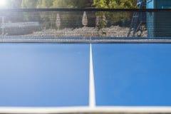 Una tabla azul de los tenis de mesa con una línea blanca en el centro y una rejilla en el borde, fondo Imagen de archivo