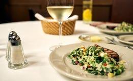 Una tabla blanca en un restaurante con una copa de vino, placa del aperitivo del tocino y ensalada, y botella de sal y de pimient foto de archivo
