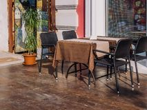 Una tabla con las sillas de una silla cerca de la ventana de un café del verano imagen de archivo
