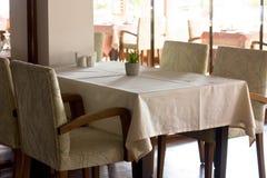 Una tabla con un mantel beige en un restaurante rodeado por AR Foto de archivo