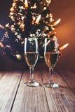Una tabla de la Navidad con los vidrios y el árbol de navidad del champán en fondo Foco selectivo Fotos de archivo