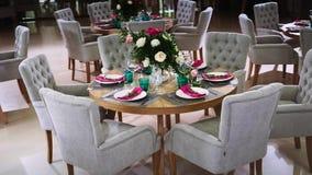 Una tabla de madera redonda adornada con las medidas florales tomadas de las placas blancas con las servilletas rosadas alrededor metrajes