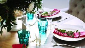 Una tabla de madera redonda adornada con las medidas florales tomadas de las placas blancas con las servilletas rosadas alrededor almacen de metraje de vídeo